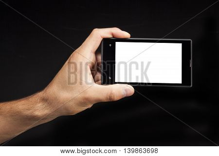Hand man holding White Smartphone with blank screen on black background