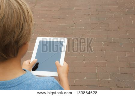 People education technology concept - boy use tablet pc computer outdoor. Close up. Copy space for text.