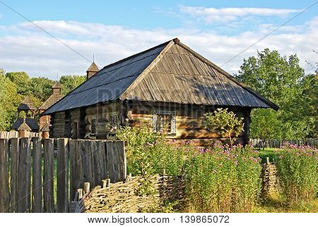 Ancient traditional ukrainian wooden rural cottage and fence