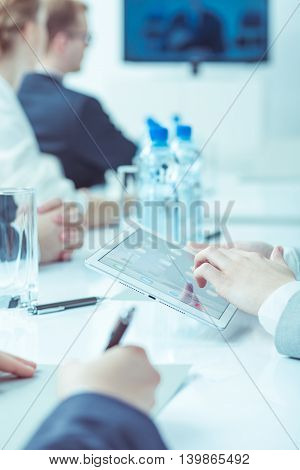 Close-up of a conference table during a corporate meeting with one participant using a tablet