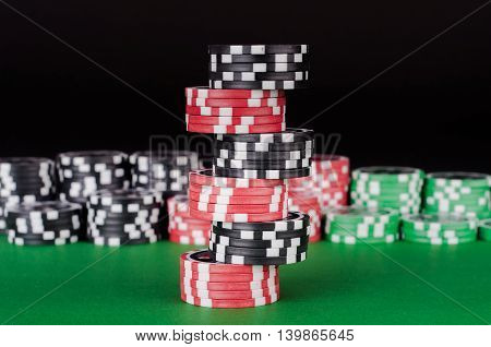 Black, Red And Green Casino Chips On Table