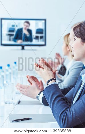 Members of the business conference clapping hands and smiling in a conference room