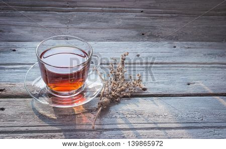 Transparent cup of black tea and dry twig herb on wooden background with copy space. Toned
