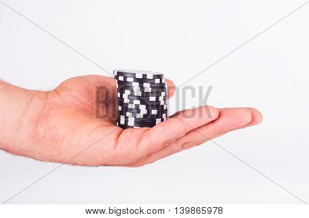 Black Casino Chips On Human Hands Isolated On White