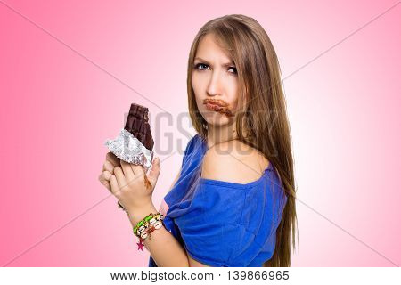 pretty woman eating chocolate with two hands, with some in her mouth. Pink background.
