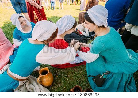 Dudutki, Belarus - July19, 2014: Participants of festival of medieval culture resting in shadow tree