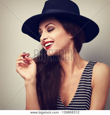 Happy toothy laughing female profile in black elegant hat. Toned vintage closeup portrait