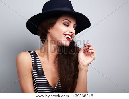 Happy toothy laughing female profile in black elegant hat on blue background
