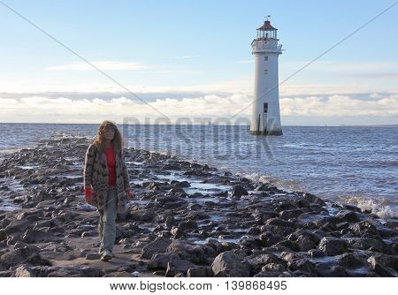 NEW BRIGHTON ENGLAND JUNE 29. The Perch Rock Lighthouse on June 29 2016 in New Brighton England. A woman walks near to the Perch Rock Lighthouse in New Brighton Merseyside England