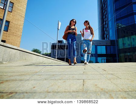Low camera angle shot of two attractive female friends walking along the street and talking on a sunny summer day