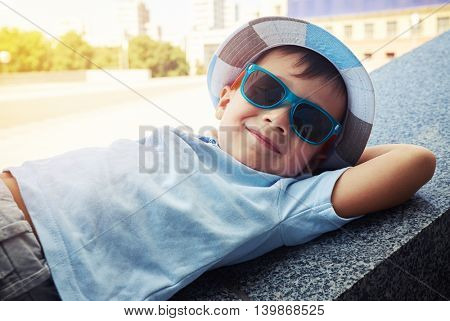 Cheerful little boy in sunglasses and hat is resting on street stairs parapet with hands under his head on a sunny day
