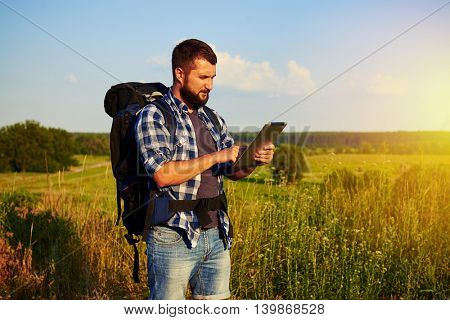 Handsome bearded man in casual clothes with rucksack behind his back is watching something on his data tablet while having a walk in rural area