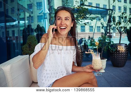 Attractive young woman is sitting on open terrace of mirror glass modern building with cocktail in her hand and speaking joyfully on the phone