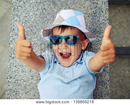 Small boy in sunglasses and hat is lying on the street stairs parapet and giving thumbs up