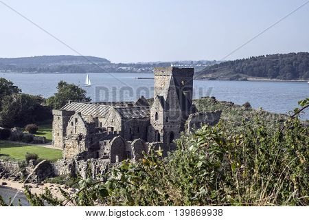 View over Inchcolm Abbey to a sailing boat on the Firth of Forth and Fife beyond