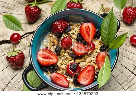 Healthy Breakfast. Oatmeal with muesli and fruit fresh strawberries, cherries and prunes with honey on the cut surface of wood