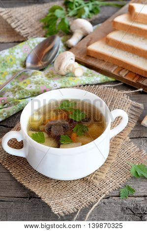 Low calorie soup with mushrooms, potatoes, carrots and parsley. Delicious easy mushroom soup in a bowl and on burlap. Pieces of bread, spoon, parsley, fresh agaricus on a wooden table