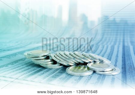 Business Concept, Coin Stacks On News Paper With Cityscape Background.