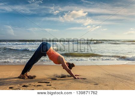 Yoga outdoors - young sporty fit woman doing Ashtanga Vinyasa yoga asana Adho mukha svanasana - downward facing dog - at tropical beach on sunset. Kerala, India