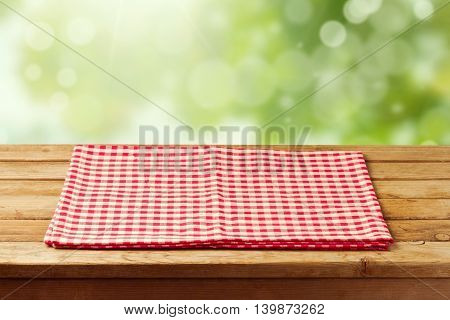 Empty wooden table with red checked tablecloth over garden bokeh background. Ready for product montage