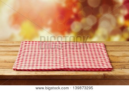 Empty wooden table with red checked tablecloth over autumn leaves bokeh background. Ready for product montage