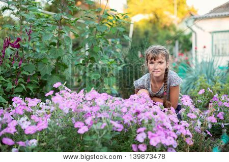 Smiling girl sitting in the garden among the flowers. Beautiful evening blurred background.