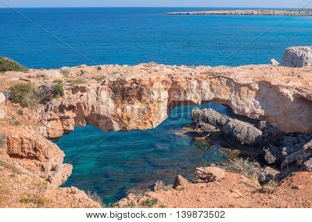 Natural stone bridge over the sea a beautiful sunny day. Bridge of sinners Cyprus Cape Greco Cavo Greco.