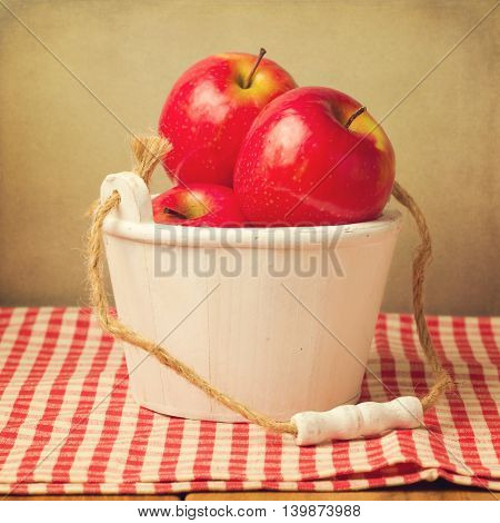 Fresh red apples in wooden bucket over checked tablecloth