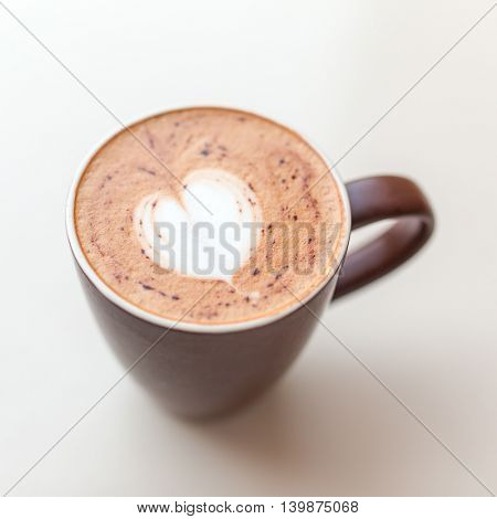 Cup of cappuccino coffee with the milky foam on top in a heart shape viewed from above in a brown cup on white table