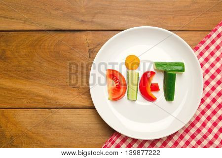Vegetables on plate over wooden tabletop with copy space. Diet concept