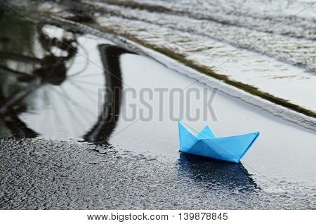 small Blue paper boat sailing on the big swings waves