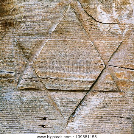 Jewish symbol David star cut on wooden surface