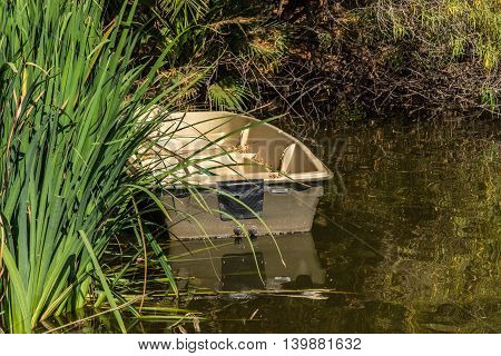 empty boat and its reflection in quiet water in forest