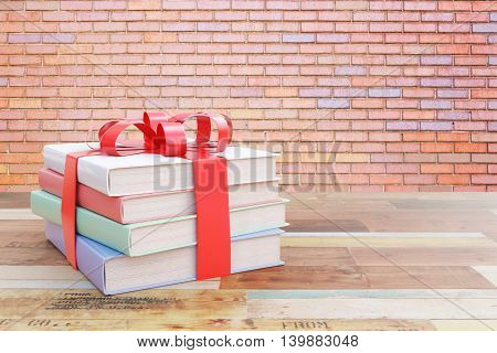Aged wooden surface with stack of colorful books tied up with a ribbon as a present on red brick wall background. 3D Rendering