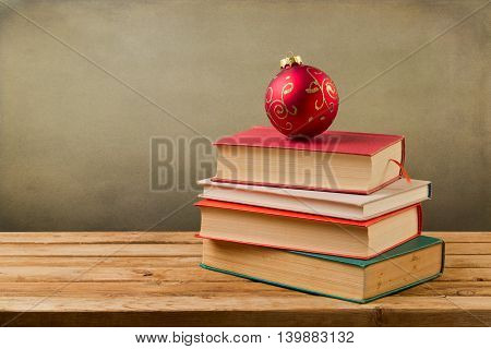 Vintage books with Christmas ornament bauble on wooden table over grunge background