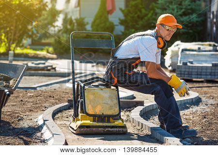 Brick Paver Worker Resting on His Soil Plate Compactor While at Work.
