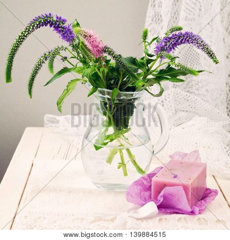 Flowers and lavender soap on wooden white table