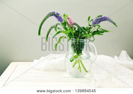 Flowers in glass jug on wooden table with lace textile