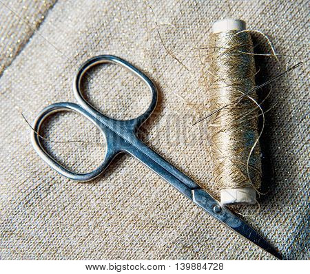 Accessories for sewing on dark golden textile thread, scissors.
