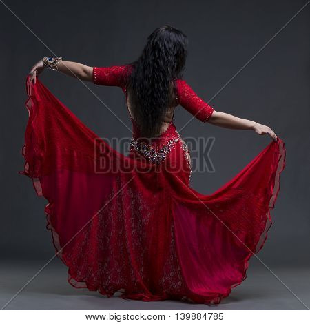 Young beautiful exotic eastern women performs belly dance in ethnic red dress with open back on gray background studio shot