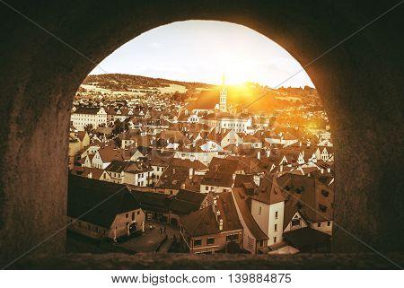 Cesky Krumlov Panorama Through The Castle Wall Window. Cesky Krumlov Czechia Europe. Sepia Color Grading.