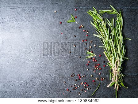 Fresh organic rosemary and black, red, white pepper on dark stone board
