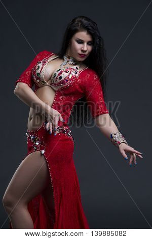 Young beautiful exotic eastern women in ethnic red dress on gray background. Studio shot