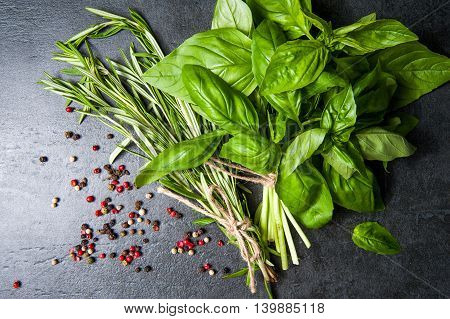 Herbs and spices. basil, red, black, white, green pepper and rosemary on a black background.
