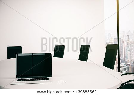 Conference table with blank laptop computer. Empty wall and window with city view in the background. Mock up 3D Rendering