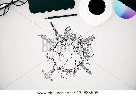 Top view of white office desktop with globe and sights sketch and other items. Travel concept