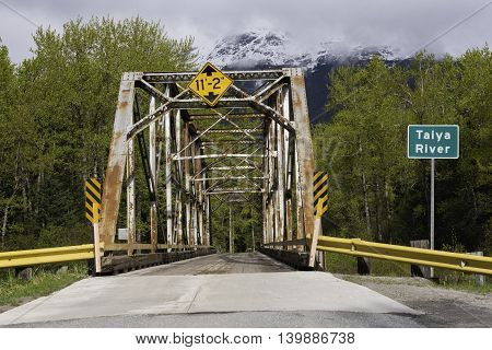 Skagway Alaska USA--April 29 2016 Rusty Steel Bridge over the Taiya River in Skagway Alaska