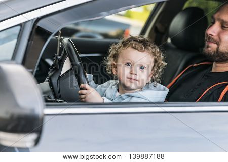 Little girl sitting in the car, on the lap of his father
