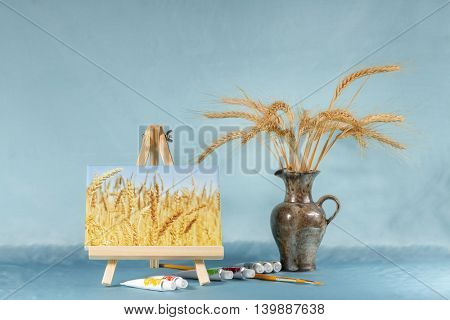 Still life with easel , watercolor and wheat ears.  Digital picture on an easel stylized watercolor.