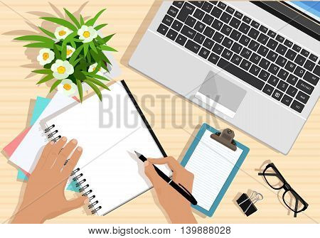 Top view of table with laptop, papers, tablet, flowers, eyeglasses and hands with pen. Modern graphic business workplace. Flat style vector illustration.